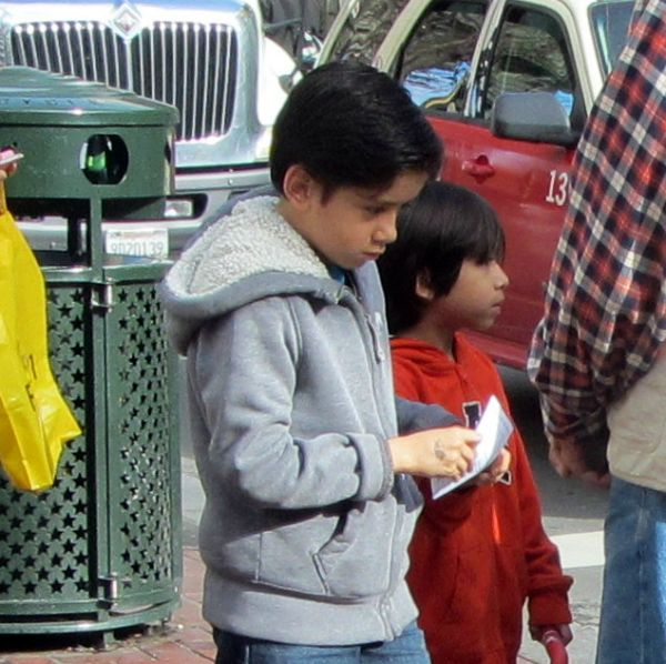 A BOY READS A TRACT AT 5TH ST AND MARKET.